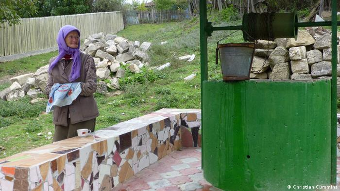 A picture a well in rural Moldova with a woman standing to the left of the well.