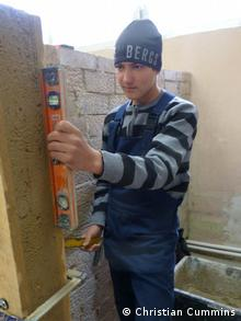A picutre of a young apprentice dressed in blue overalls and a stripey shirt learning vocational skills at a school near Chisinau