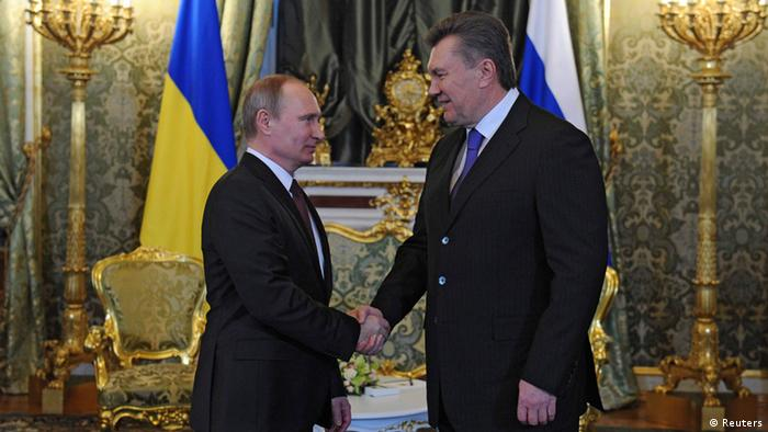Russian President Vladimir Putin shakes hands with Ukrainian President Viktor Yanukovych in an ornately decorated palatial room.