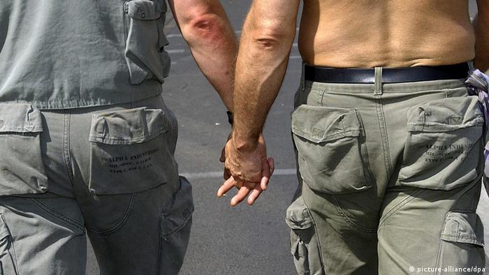 Двое мужчин - участники гей-парада в Берлине в военной форме - держатся за руки