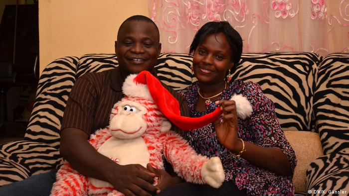 A man and woman seated in a sofa seat while holding a mascot of father Christmas.
