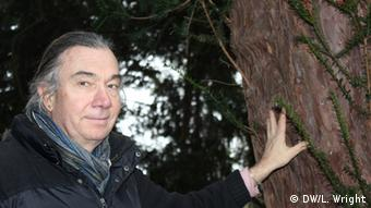 Wolfram Lobin, curator of the University Botanical Gardens in Bonn, leans against the trunk of an evergreen tree.
