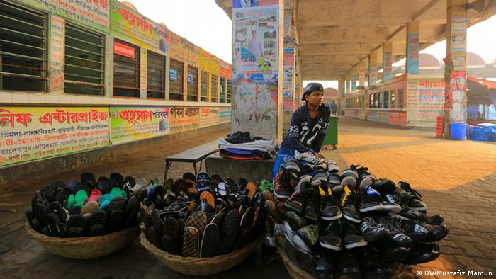 A young man sits waiting for customers behind a pile of shoes