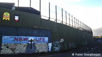 A picture from West Belfast showing high walls and fencing alongside one of the marching routes.