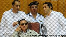 Egyptian toppled president Hosni Mubarak and his two sons Alaa (R) and Gamal stand behind bars during their trial at the Police Academy on September 14, 2013 in Cairo. Mubarak appears in court for the second time since his release from Cairo's Tora prison and he faces an array of charges, including complicity in the deaths of some 850 people killed in the Arab Spring-inspired uprising against him, and corruption. AFP PHOTO / AHMED EL-MALKY (Photo credit should read AHMED EL-MALKY/AFP/Getty Images)