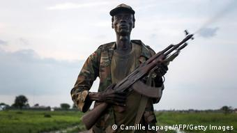 A Lou Nuer fighter holding an assault weapon and wearing combat wear.