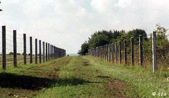 A wide grassy path lined by barbed wire on both sides