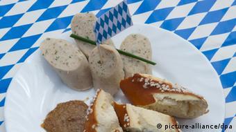 Weißwürste geschnitten mit Senf auf einem Teller, der auf einer Decke in den bayrischen faren blau-weiß steht
