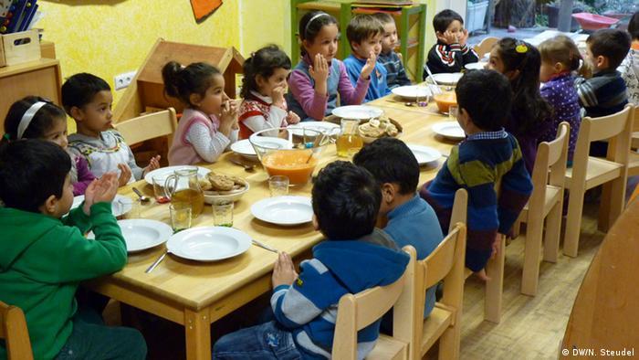 Kinder im muslimischem Kindergarten beim Mittagessen und beten (Foto: DW)