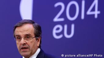 Greek Prime Minister Antonis Samaras in front of a purple banner reading 2014 EU