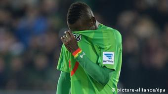 Mame Biriam Diouf buries his head in his jersey after Hanover's away defeat to Freiburg, 21.12.2013. (Photo via Patrick Seeger/dpa)
