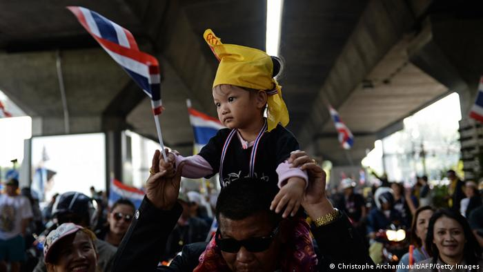 A Thai anti-government protester carries his child on his shoulders as protesters march through the streets of Bangkok as part of their ongoing rally on December 22, 2013. (Photo via CHRISTOPHE ARCHAMBAULT/AFP/Getty Images)