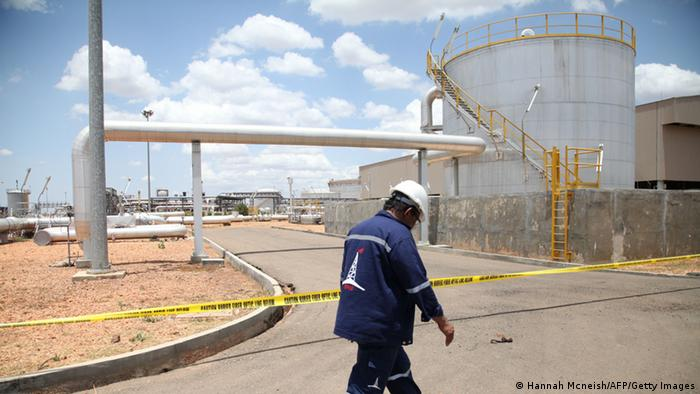 A worker walks past an oil production facility in South Sudan's Upper Nile state - FILE