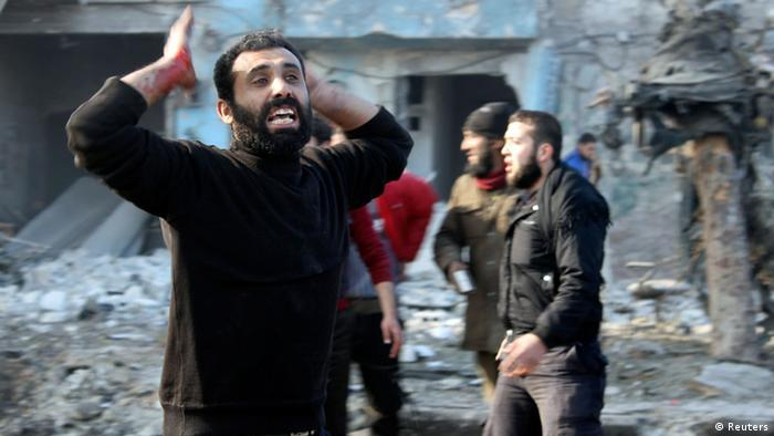 A man with blood stained hand reacts at a damaged site after what activists said was heavy shelling by forces loyal to Syrian President Bashar Al-Assad, in Masaken Hanano neighbourhood in Aleppo December 22, 2013. REUTERS/Hosam Katan