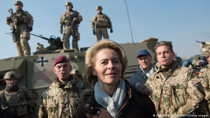 German Defense Minister von der Leyen is standing in front of soldiers and a tank.