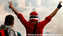 An Egyptian protester makes the sign of the victory during protests near Cairo's Tahrir Square on January 27, 2013. Clashes killed at least 31 people in Egypt's Port Said as violence raged in several cities including the capital following death sentences passed on 21 football fans after a riot. AFP PHOTO/MOHAMMED ABED (Photo credit should read MOHAMMED ABED/AFP/Getty Images)