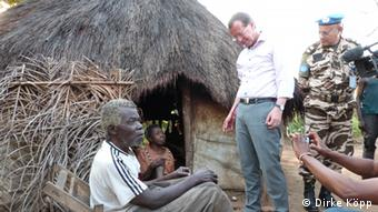 Martin Kobler talks to displaced people outside their hut