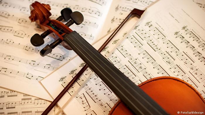 Eine Violine liegt auf einem Heft mit musikalischen Noten