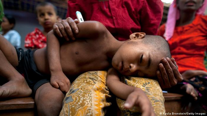 Criança de aparência doente deitada no colo da mãe