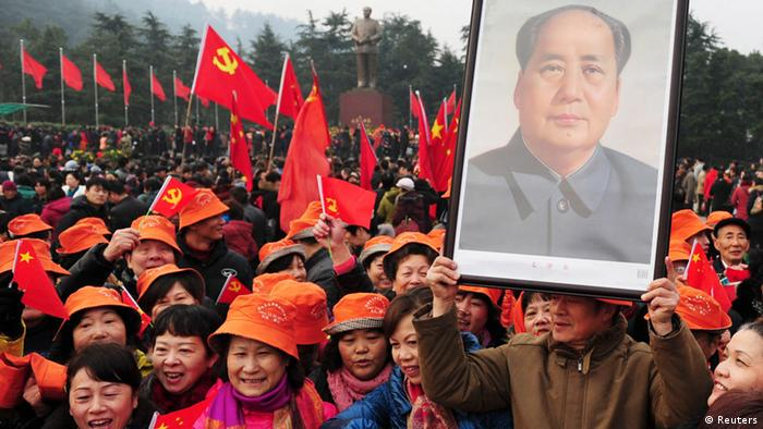 A man holds up a portrait of the late Chairman Mao Zedong as he and others gather in front of a giant statue of Mao on a square to celebrate the 120th birth anniversary of the former leader, in Shaoshan, Mao's hometown, December 26, 2013. Thursday marks the 120th anniversary of Mao's birth, with various commemorative activities scheduled to be carried out throughout the nation. Photo: REUTERS