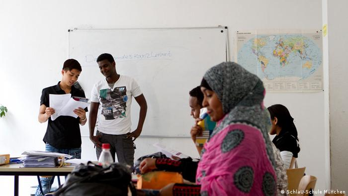 Two refugee children stand at a whiteboard in a classroom
