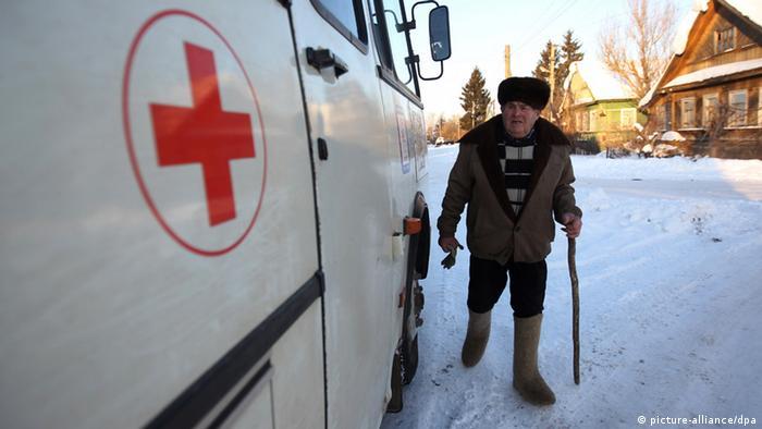 Пожилой человек подходит к мобильному медпункту в заснеженной деревне