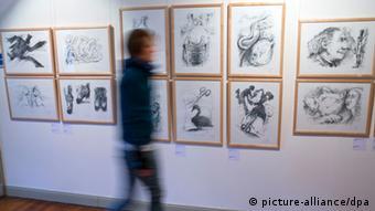 Eine Frau geht in der Günter-Grass-Schau an Litografien vorbei