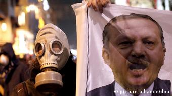 Turkish protestor wearing a gas mask holds a banner with a portrait of Turkish Prime Minister Recep Tayyip Erdogan (R) during an anti-government protest in Istanbul (photo: EPA/SEDAT SUNA +++(c) dpa - Bildfunk)