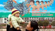 A Chinese woman lifts her child in front of a family planning propaganda advertisement in Xinshao county, central Chinas Hunan province, February 2005. Foto: Lv jianshe/Imaginechina +++(c) dpa - Report+++