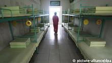 --FILE--A Chinese inmate walks past beds in a room at a female labor camp in Jurong city, east Chinas Jiangsu province, 6 March 2008. Meng Jianzhu, who became secretary of the Political and Legal Affairs Committee in November, said at a national law and order work conference that the re-education through labour, or laojiao, system would be halted after the move was rubber-stamped by the National Peoples Congress in March. The remarks were first reported by the bureau chief of the Legal Daily, the Justice Ministrys official mouthpiece, and were picked up by state media outlets. An official who attended the event confirmed Mengs comments. But state media sent mixed signals about the policy. A Xinhua report on the conference said only that authorities had pledged to reform the system, and some analysts noted that Meng spoke of halting rather than abolishing the laojiao system.