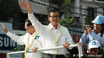 Opposition leader Sam Rainsy (centre) and his deputy, Kem Sokha, wave as they lead tens of thousands of protesters along Monivong Boulevard in Phnom Penh