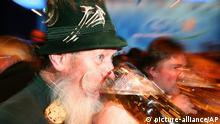 Symbolbild: Ein bayrischer Mann in Tracht und einem grauen Bart trinkt Bier aus einer Maß