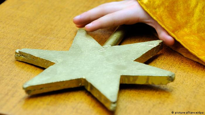 Child's hand holding a gold-painted star cut from spare wood. (Photo: picture alliance/dpa)