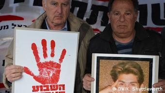 Yakov Tuboul with a fellow protester, holds up a picture of his dead son Lior