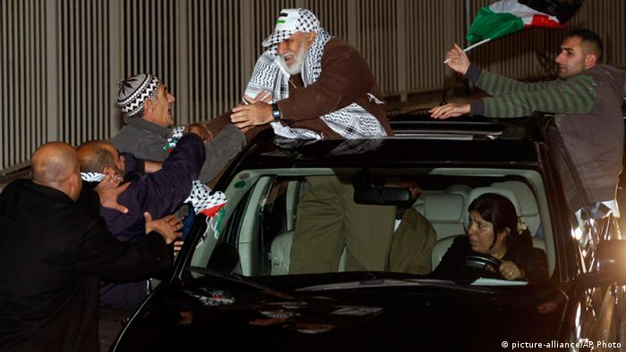 A released Palestinian prisoner in a car is greeted by family and friends