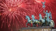 BERLIN, GERMANY - JANUARY 01: Fireworks explode behind the Quadriga statue on top of the Brandenburg Gate shortly after midnight on January 1, 2014 in Berlin, Germany. Tens of thousands of revelers gathered in the city center to celebrate New Year's Eve. (Photo by Adam Berry/Getty Images)
