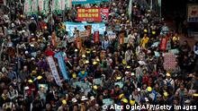 Protesters march along a street in Hong Kong during a pro-democracy demonstration on January 1, 2014. Tens of thousands of people rallied in Hong Kong to call for universal suffrage, as the city grapples with how its future leaders will be chosen under a long-awaited political reform. AFP PHOTO / ALEX OGLE (Photo credit should read Alex Ogle/AFP/Getty Images)