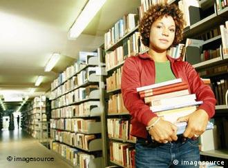 Woman in library stacks holding books