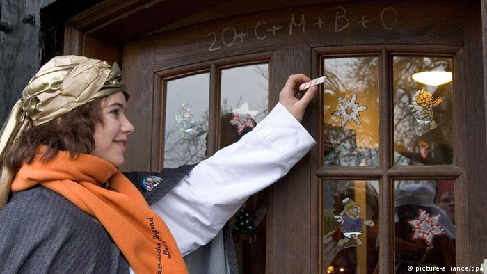 A girl in Sternsinger costume writes the blessing in chalk on a front door. (Photo: picture alliance/dpa)