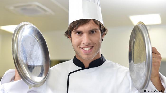 Ein Koch mit zwei Kochtopfdeckeln (Fotolia/goodluz)