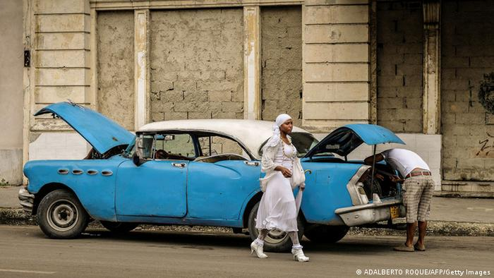 A woman walking past an ancient blue American sedan with its hood up on a Havana street, December 2013. (Photo: ADALBERTO ROQUE/AFP/Getty Images).