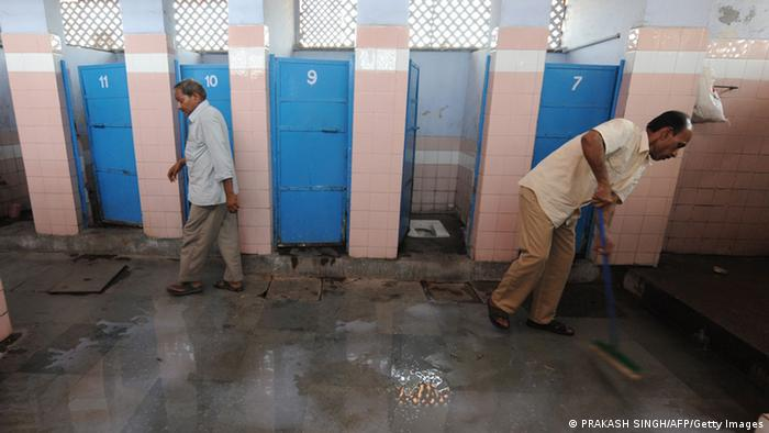 An Indian man leaves after using a toilet as a sweeper (R) cleans a toilet complex