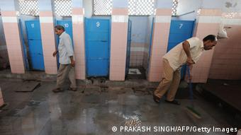 A Indian man leaves after using a toilet as a sweeper (R) cleans a toilet complex run by an NGO Sulabh International at a railway station in New Delhi on April 23, 2011 (Photo: PRAKASH SINGH/AFP/Getty Images)