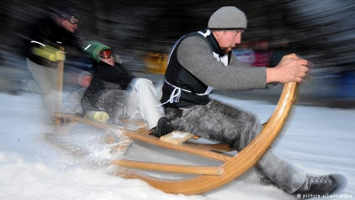 A man flies down a snowy hill on a big wooden sled