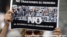 A member of the Jewish community holds a sign reading Don't betray your memory. No to the agreement with Iran's regime, outside the Congress building in Buenos Aires on February 27, 2013, while legislatives discuss the possibility of an agreement with Iran to establish a truth commission over a terrorist attack that took place in 1994. Eight Iranian nationals are still wanted in connection with the bombing of the Argentine Israelite Mutual Association (AMIA is Spanish), which left 85 dead and 300 wounded. AFP PHOTO / Juan Mabromata (Photo credit should read JUAN MABROMATA/AFP/Getty Images)