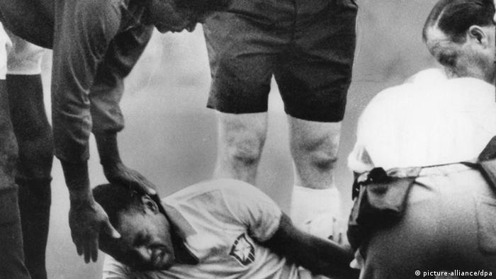 Brasiliens Stürmerstar Pele liegt am 19.7.1966 im Liverpooler Goodison Park mit schmerzverzerrtem Gesicht gefoult am Boden und wird von Betreuern behandelt; Portugals Stürmerstar Eusebio tröstet ihn (Foto: dpa)