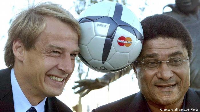 Deutschlands Stürmer- und Trainerstar Jürgen Klinsmann und Eusébio halten zur EM 2004 einen Fußball zwischen ihren Köpfen (Foto: picture-alliance/AP Photo)