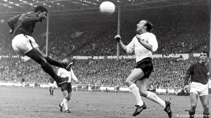 Portugals Torjäger Eusebio köpft vor dem englischen Mittelfeldspieler Nobby Stiles und seinem Teamgefährten Augusto auf das englische Tor im Halbfinalspiel am 26.07.1966 im Londoner Wembleystadion (Foto: dpa)