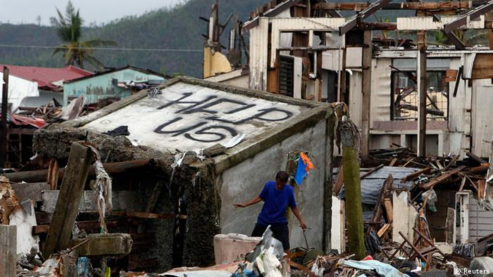 A victim of super typhoon Haiyan walks past a devastated area of San Jose town, Tacloban city, central Philippines December 22, 2013 (Phot: REUTERS/Romeo Ranoco)