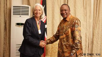 Wearing a business suit, Christine Lagarde shakes hands with Uhuru Kenyatta, wearing brown African robes.